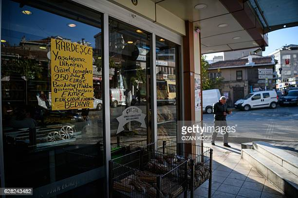 A placard on a backery's window reads 'free bread for who exchange 250 US dollars/euros to Turkish liras' in Istanbul on December 6 2016 Convert your...
