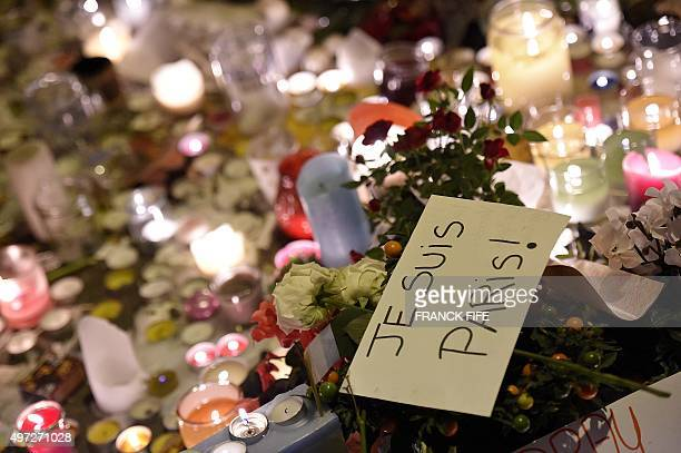A placard reading 'I am Paris' is seen among flowers and candle at a makeshift memorial in front of the Bataclan theatre one of the site of the...