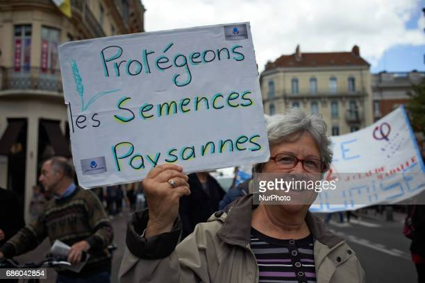 A placard reading 'Let's us protect farmer' seeds' People march in Toulouse for the International March against Monsanto as elsewhere in Europe or in...