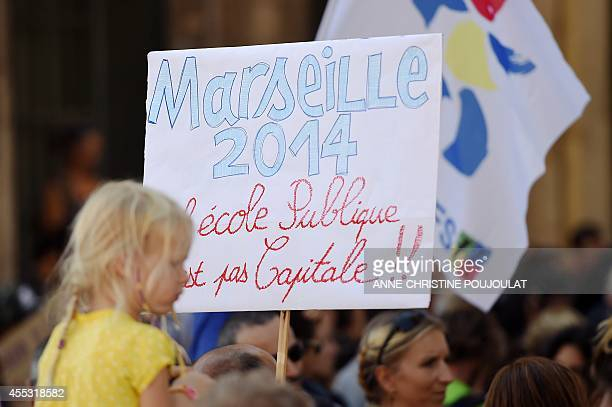 A placard reading 'Public school is not crucial' during a demonstration by parents and children in front of Marseille's city hall one week after the...