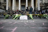 A placard reads 'Share your love' next to flowers and candles laid on the ground at a makeshift memorial following attacks in Brussels on March 22...