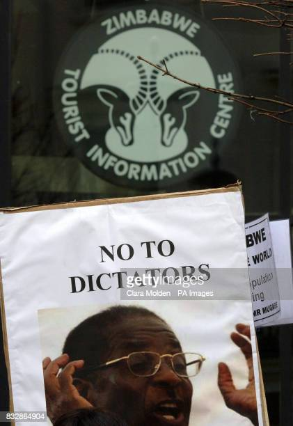 A placard showing Robert Mugabe's face and reading 'No to dictators' is seen before the sign for the Zimbabwe tourist information centre during a...