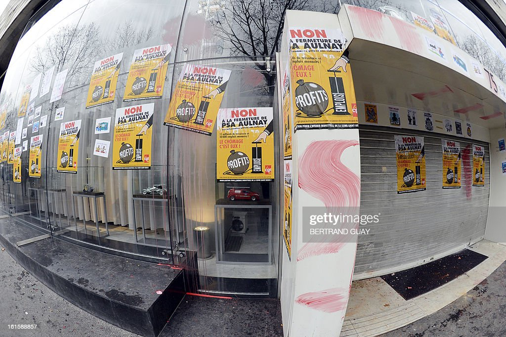 Placards have been set by workers of PSA Peugeot Citroen on the facade of the group's headquarters, on February 12, 2013 in Paris, during a demonstration to protest against the group's restructuration plan which involves more than 11.200 job cuts in France, at the time of a negociation meeting on the social support measures accompanying the plan.