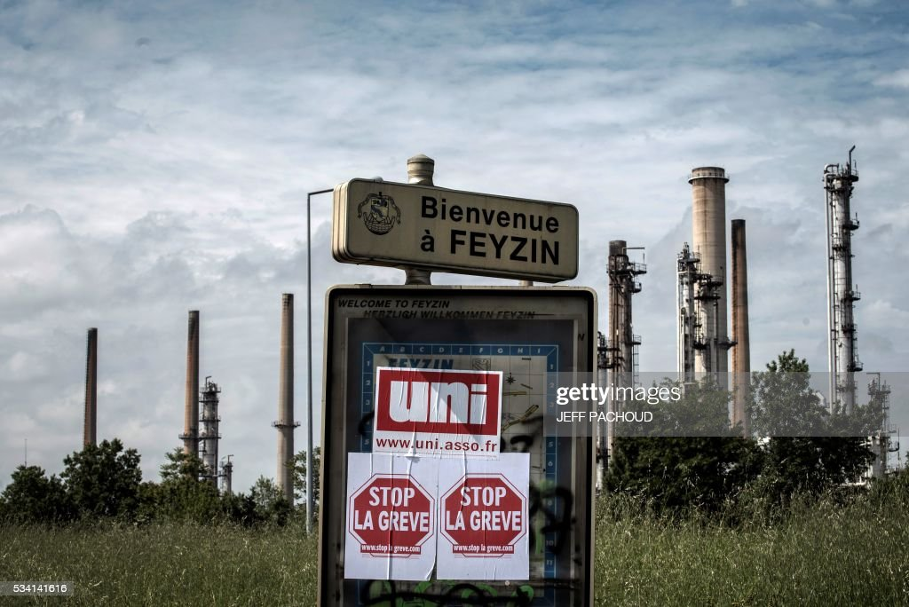 Placards reading 'Stop the strike' are stuck on a board in front of the Total refinery of Feyzin, on May 25, 2016 during a protest against the government's planned labour law reforms. France has been using strategic fuel reserves for two days in the face of widespread blockades of oil depots by union activists, the head of the oil industry federation said on May 25, 2016. PACHOUD
