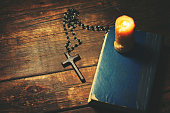 cross, book and candle on wooden background