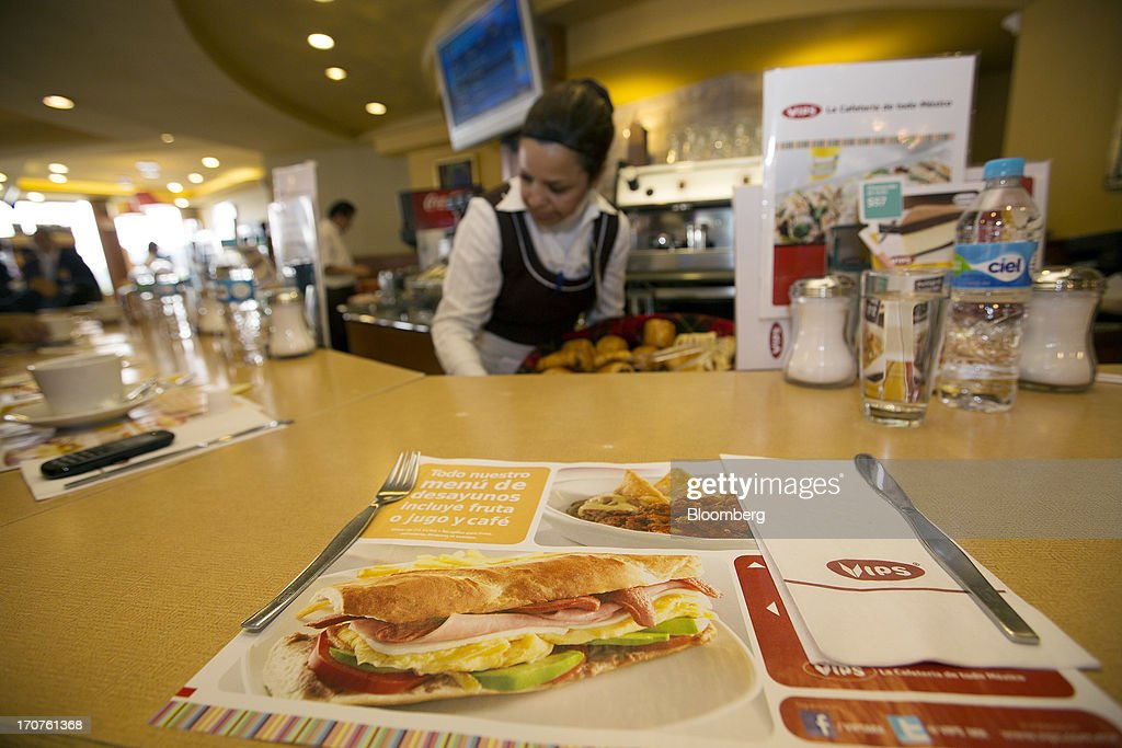 A place mat sits on the counter while a waitress works at a Vips restaurant in the El Toreo neighborhood of Mexico City, Mexico, on Monday, June 17, 2013. Wal-Mart de Mexico SAB de CV, known as Walmex, is considering offers to sell its restaurant division, which includes the Vips, El Porton, Ragazzi and La Finca brands. Photographer: Susana Gonzalez/Bloomberg via Getty Images