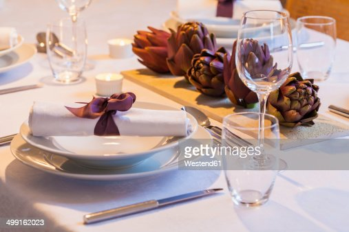 Place setting and decoration with artichokes on festive laid table