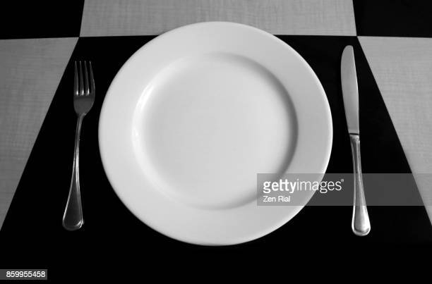 Place setting on a dinner table with geometric designs in black and white