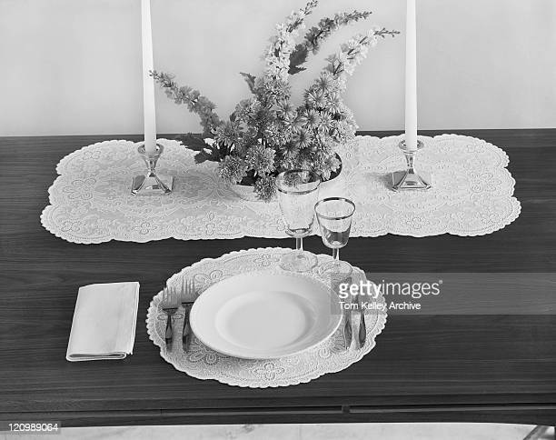 Place setting with candles, flowers, plate and glasses