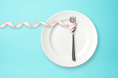 Place setting with steel fork and measuring tape on blue background with copy space.