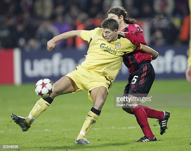 Placente of Leverkusen is held back by Steven Gerrard of Liverpool during the UEFA Champions League first knockout round second leg match between...