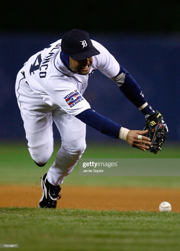 Placido Polanco of the Detroit Tigers attempts tp pick up a ball that was misplayed by Todd Jones in the ninth inning against the St Louis Cardinals...