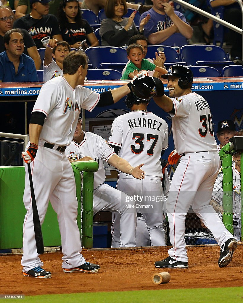 Placido Polanco #30 of the Miami Marlins is congratulated by Logan Morrison #5 after hitting an RBI sacrafice fly during a game against the New York Mets at Marlins Park on July 31, 2013 in Miami, Florida.