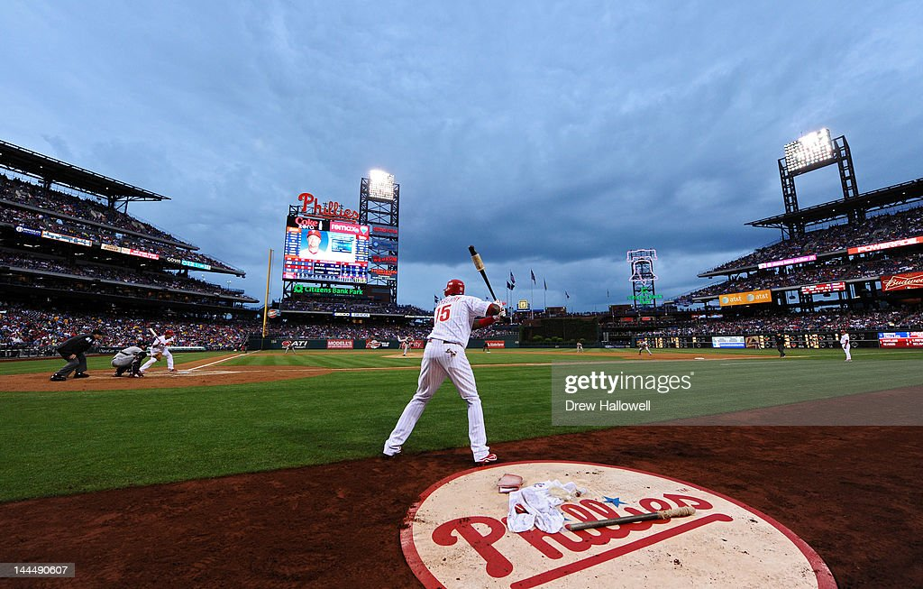 Placido Polanco of the Philadelphia Phillies bats while John Mayberry Jr #15 waits on deck and the storm clouds roll in during the game against the...