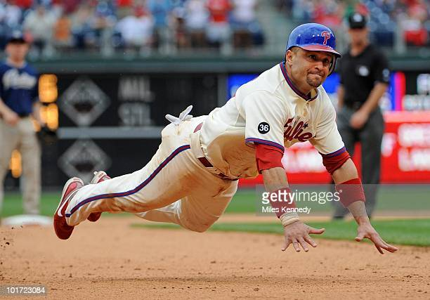 Placido Polanco of the Philadelphia Phillies dives into third base against the San Diego Padres in the tenth inning on June 6 2010 at Citizens Bank...