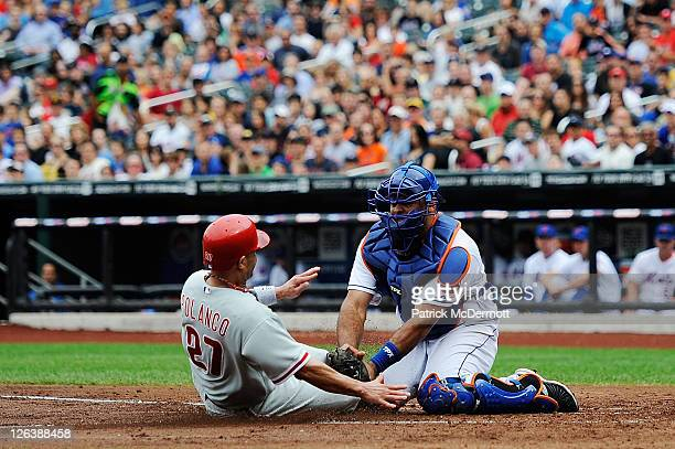 Placido Polanco of the Philadelphia Phillies is tagged out at home plate by Ronny Paulino of the New York Mets in the third inning at Citi Field on...
