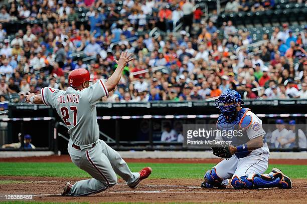 Placido Polanco of the Philadelphia Phillies slides in to home plate towards Ronny Paulino of the New York Mets in the third inning at Citi Field on...