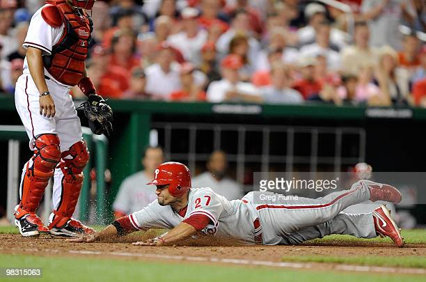 Placido Polanco of the Philadelphia Phillies slides safely into home plate in the seventh inning against the Washington Nationals at Nationals Park...