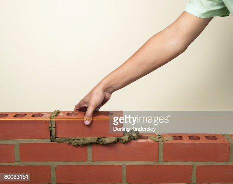 Placing a new brick on to fresh mortar on a wall : Stock Photo