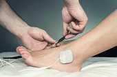 Physical therapist placing TENS electrodes on patient's foot