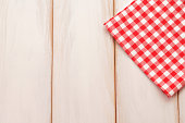 Red plaid cloth on wooden table. Food background