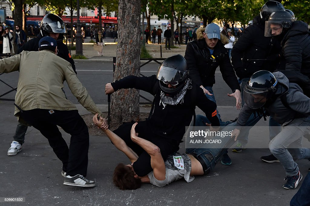 Plain cloth policemen arrest a man during clashes between anti-riot police and protesters during the traditional May Day demonstration in Paris on May 1, 2016.
