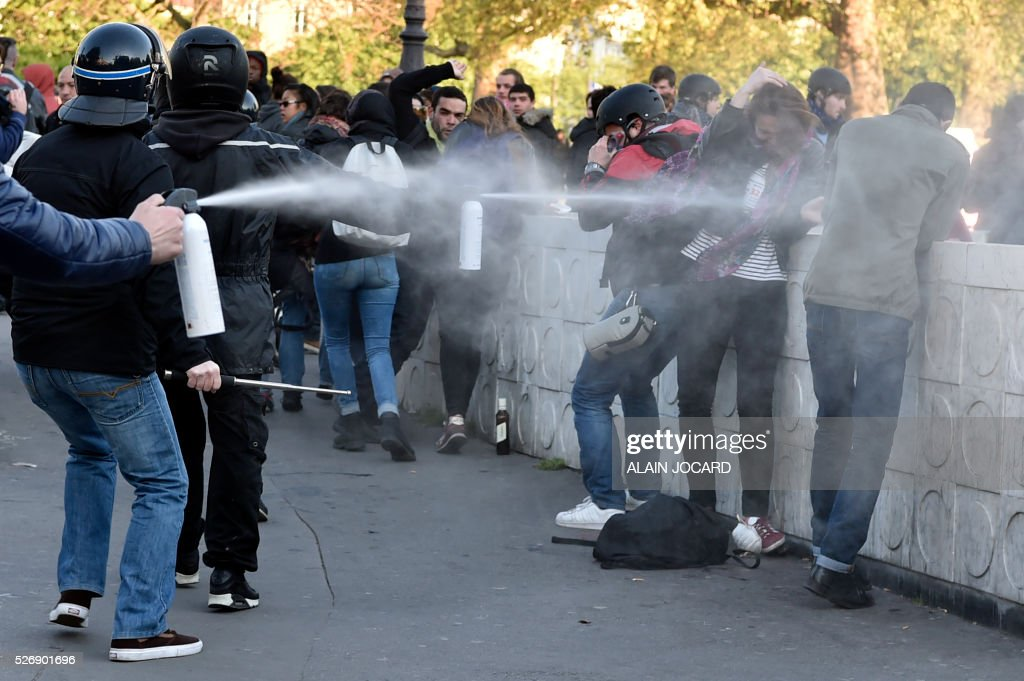 Plain cloth policemen spray tear gas at protesters during clashes between anti-riot police and protesters during the traditional May Day demonstration in Paris on May 1, 2016.