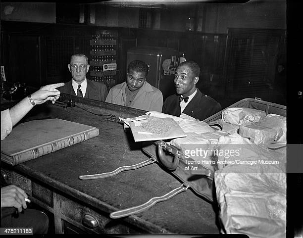 Plain clothes police officer Ray Miller suspect Fred Moore police patrolman Oliver Mason standing before court bench with opened suitcase with...
