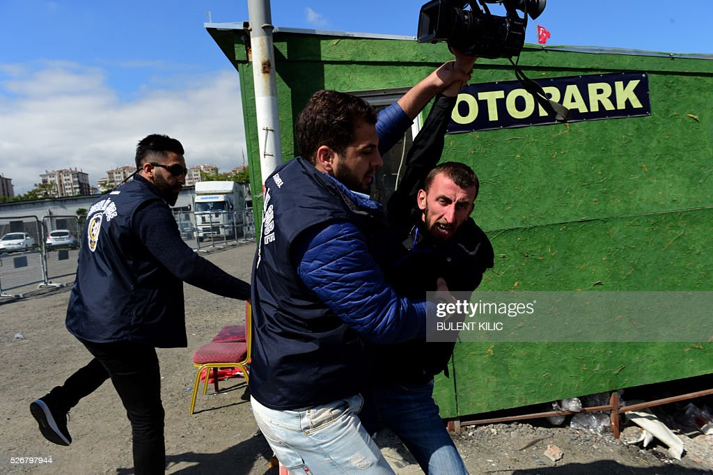 Plain clothes police officers block a journalist as he attempts to film protesters detained by Turkish Police during a May Day rally in Bakirkoy district of Istanbul, on May 1, 2016. Turkish labour activists and leftists marked the annual May Day holiday, with thousands of security deployed and bracing for trouble after the authorities refused to allow protests in central Taksim Square. / AFP / BULENT