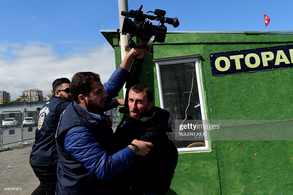 Plain clothes police officers block a journalist as he attempts to film protesters detained by Turkish Police during a May Day rally in Bakirkoy, a district of Istanbul, on May 1, 2016. Turkish labour activists and leftists marked the annual May Day holiday, with thousands of security deployed and bracing for trouble after the authorities refused to allow protests in central Taksim Square. / AFP / BULENT