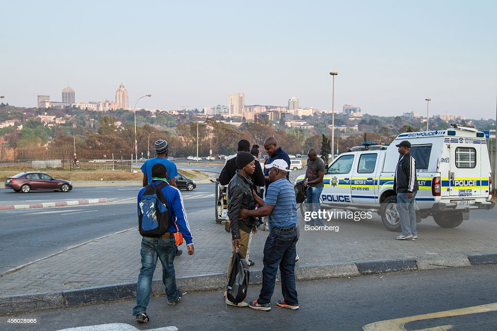 Plain clothes police officers stop and search pedestrians as they walk along a highway from Alexandra township towards Sandton in Johannesburg South...