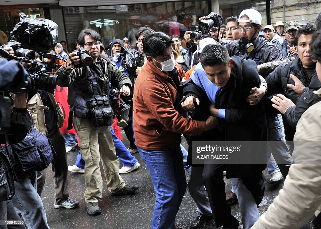 A plain clothes policeman is aggressed by workers during a protest on the 12th day of an indefinite strike called by the Bolivian Workers' Central union (COB) to demand the government for a pension equivalent to 100% of their salaries, in La Paz on May 17, 2013. AFP PHOTO/Aizar Raldes