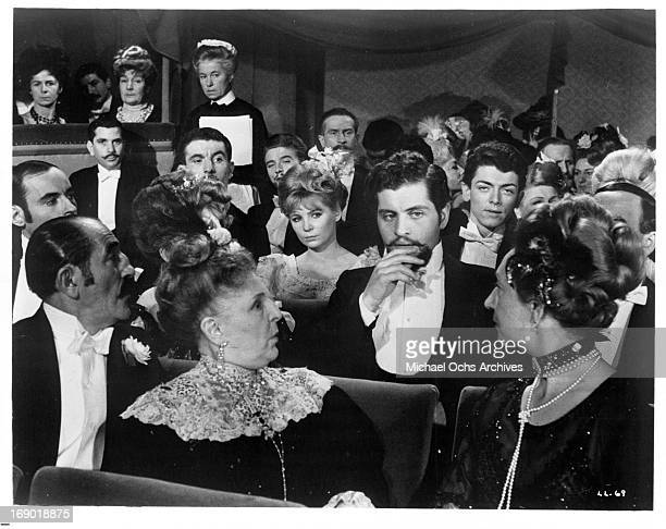 Plain clothes policeman Joseph Dassin tries to attract the attention of a colleague seated two rows in front in a scene from the film 'Lady L' 1965
