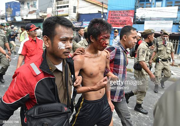 Plain clothes policemen and civil security personnel arrest a resident during a demolition of some 150 shanty houses along the river bank in Jakarta...