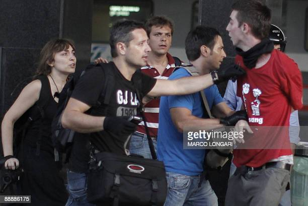 Plain clothes policemen arrest a protester on a quay of Termini station after clashes during a demonstration against the upcoming G8 summit on July 7...