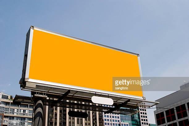 Plain orange billboard amongst office buildings