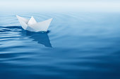 paper boat sailing on blue water surface.