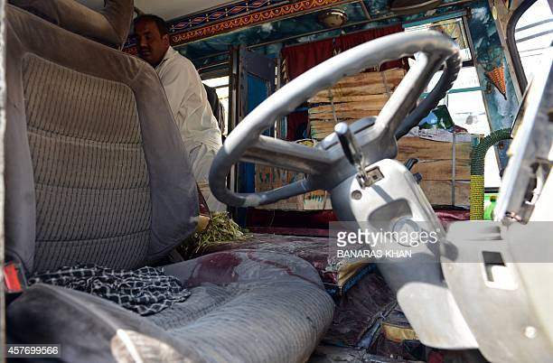 A plainclothed Pakistani police official examines a passenger mini bus after an attack by gunmen on the outskirts of Quetta on October 23 2014 Gunmen...