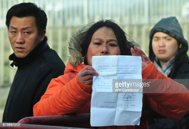 Plainclothed security personnel watch as a protester displays a document outside the courthouse at the verdict from the trial of leading Chinese...