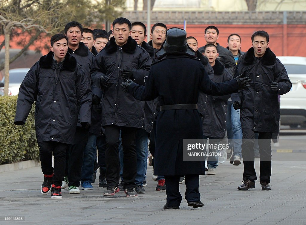 Plainclothes Chinese security reinforcements arrive to confront migrant workers after they staged a sit-in at the residence of a construction firm boss when the group of up to 50 migrant workers stormed past security at the Qijiayuan Diplomatic Compound to protest against what they claim is an unpaid new year bonus in Beijing on January 14, 2013. Labour unrest and disputes are common before the Chinese New Year when migrant workers are paid for their full years work in a lump sum before heading home to their famillies in outer provinces of the country. AFP PHOTO/Mark RALSTON