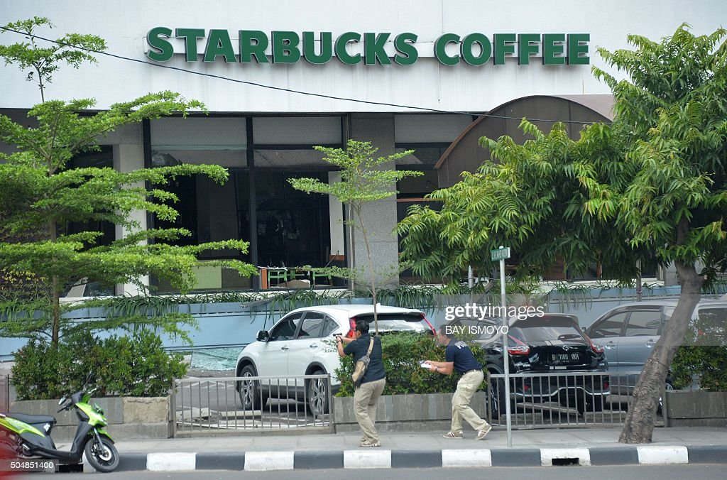 Plainclothes police aim their handguns towards suspects outside a cafe after a series of blasts hit the Indonesia capital Jakarta on January 14 2016...
