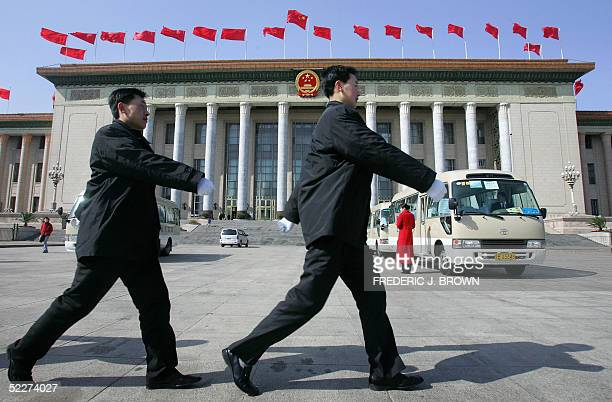 Plainclothes police march in front of the Great Hall of the People in Beijing 04 March 2005 Heavy security is in place in the Chinese capital with...
