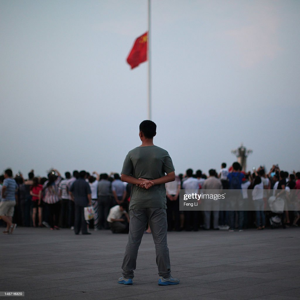 A plainclothes police officer guards behind the tourists during the customary ceremony of lowering flag at Tiananmen Square on June 4, 2012 in Beijing, China.