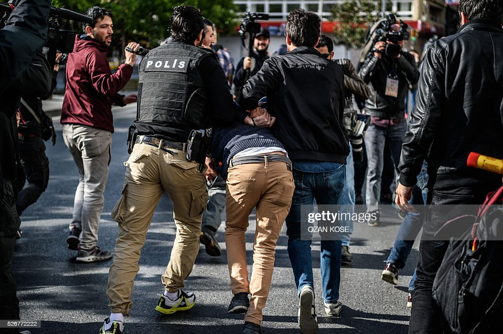 Plainclothes police officers detain a demonstrator during a May Day rally in Sisli, a district of Istanbul, on May 1, 2016. Turkish labour activists and leftists marked the annual May Day holiday, with thousands of security deployed and bracing for trouble after the authorities refused to allow protests in central Taksim Square. / AFP / OZAN