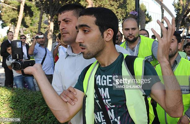 Plainclothes police officers detain a man identified as a journalist of an opposition media during a protest in Baku on May 25 2012 Azerbaijan hosts...