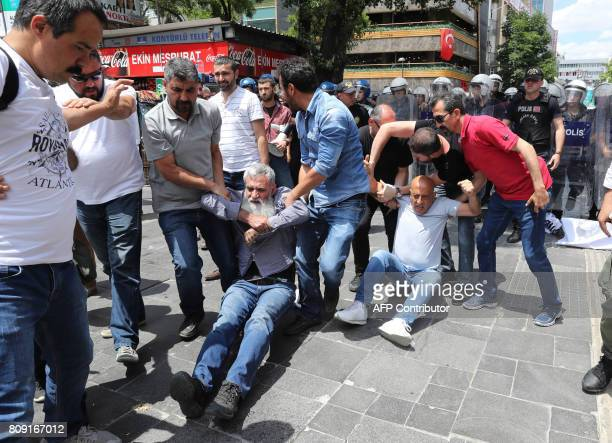 Plainclothes police officers detain demonstrators during a protest against the detention of two hungerstriking teachers in Ankara on July 5 2017 A...