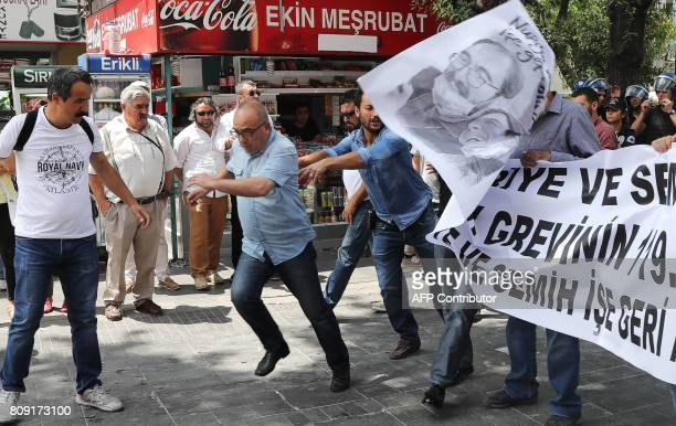 Plainclothes police officers take down a banner during a protest against the detention of two hungerstriking teachers in Ankara on July 5 2017 A...