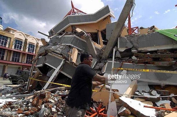 A plainclothes policeman secures the area around a destroyed building in Banda Aceh 27 December 2004 after a devastating quake and series of tidal...