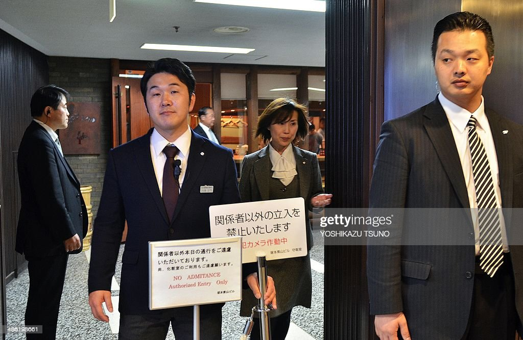 Plainclothes policemen stand guards at the entrance of sushi restaurant 'Sukiyabashi Jiro' in Tokyo on April 23, 2014. US President Barack Obama will reportedly dine at a tiny Tokyo sushi restaurant, a place with three coveted Michelin stars but only a handful of seats, ruled with an iron rod by its redoubtable 88-year-old owner, Jiro. Obama will come to Tokyo for a three-day visit from April 23 for and will have dinner with Japanese Prime Minister Shinzo Abe. AFP PHOTO / Yoshikazu TSUNO