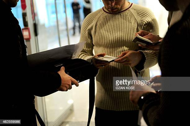 Plainclothes Turkish police officers check passengers' passports after a plane landed at the international airport in Istanbul on January 29 2015 The...
